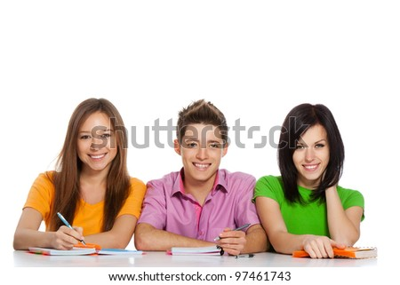 young group of people sitting at the desk, study, learning books, write, read, smile, three students looking at camera, isolated over white background - stock photo