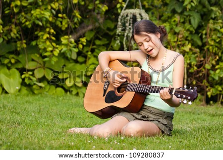 Young guitarist in the park, playing the guitar and singing - stock photo
