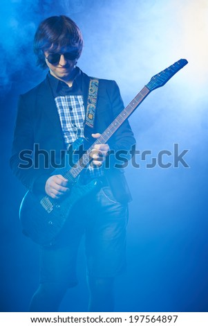 Young guitarist performing on stage, smoky scenic - stock photo