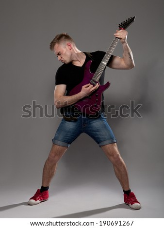 Young guitarist plays on the electric guitar with bright emotions - stock photo
