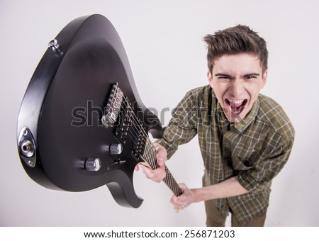 Young guitarist with the electric guitar in studio. - stock photo