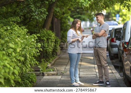 Young guy and girl jokingly talking on the street. - stock photo