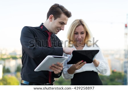 young guy and girl with the tablet on the background of the city - stock photo