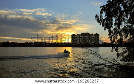 Young guy cruising in the lake on a jet ski during sunset. - stock photo