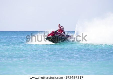 Young guy cruising on a jetski on the caribbean sea - stock photo