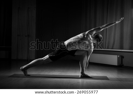 young guy doing yoga in the gym, black and white - stock photo