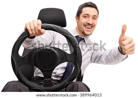 Young guy driving and giving a thumb up isolated on white background - stock photo