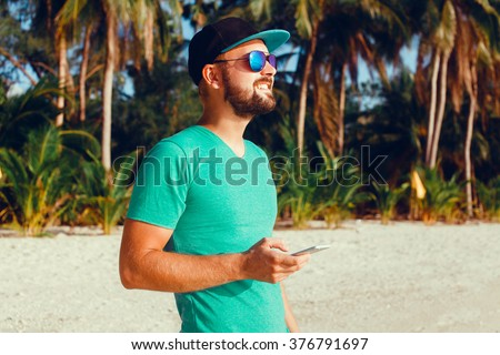 young guy in sunglasses t-shirt talking on the smartphone to respond to messages texting,I love selfie! holding camera smiling while standing against grey background outdoor portrait, close up,bearder - stock photo