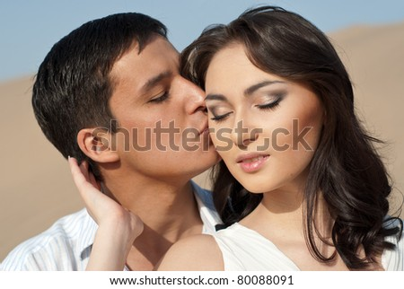 Young guy kissing a beautiful young girl. Young couple in white - stock photo