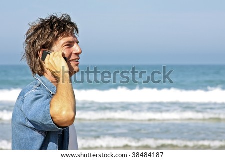 Young guy making a phonecall on the beach - stock photo