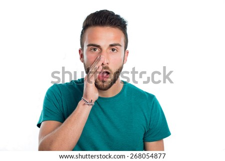 Young guy making the gesture 're telling a secret to someone with green shirt isolated on white background - stock photo