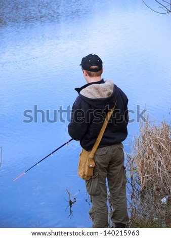 Young guy out fishing on the lake with a fishing rod - stock photo
