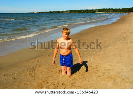 Young guy playing in the sand on the beach of Baltic Sea - stock photo