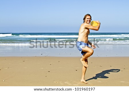 Young guy playing with frisbee at the beach - stock photo
