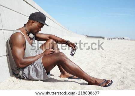 Young guy sending a text message at the beach. African man sitting on beach using mobile phone. Muscular male model outdoors. - stock photo