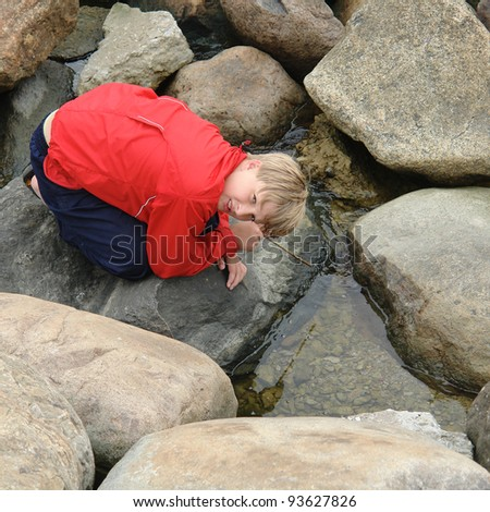 Young guy sitting alone on rock looking at camera - stock photo