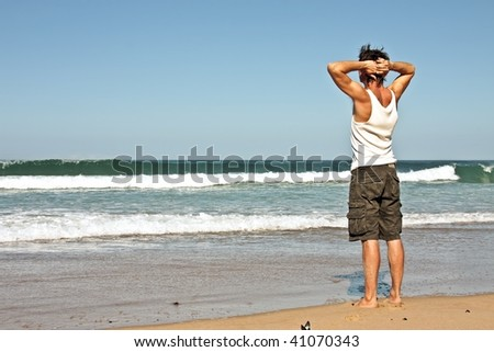 Young guy standing and contemplating the Atlantic ocean - stock photo