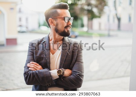young guy with a beard and mustache with glasses in a suit posing on the street in the sunlight - stock photo
