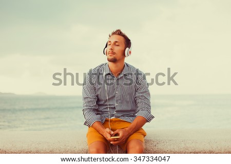young guy with a beard in a shirt and headphones,Young and smiling man sitting on the roof with mobile phone and listening music (intentional sun glare and vintage color, focus on mobile phone - stock photo
