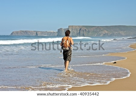 Young guy with backpack having a walk at the beach along the atlantic ocean - stock photo