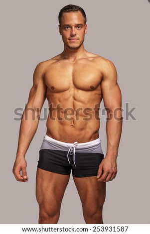 Young guy with great body anatomy in black swim shorts possing in studio. Light grey background. - stock photo