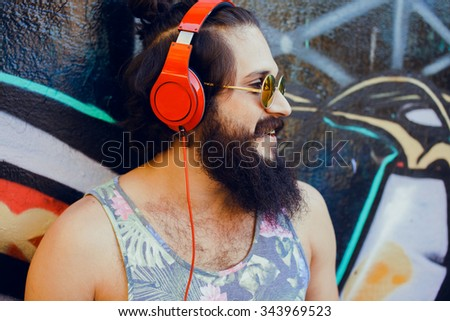 young guy with long hair mustache and beard listening to music with headphones - stock photo