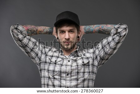 young guy with tattoos and piercings in the ears, holding his hands behind his head and looks directly into the camera. Dressed in a plaid shirt and a black baseball cap - stock photo