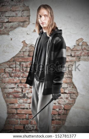 Young guy with telescopic baton, trying to make a living from crime. - stock photo