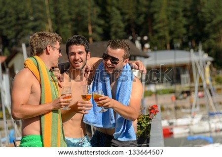 Young guys toasting with beer enjoying summer in swimsuits - stock photo