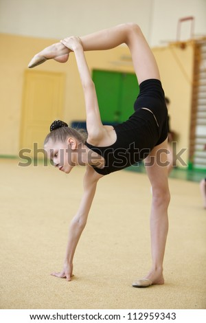 young gymnast stretching and training - stock photo