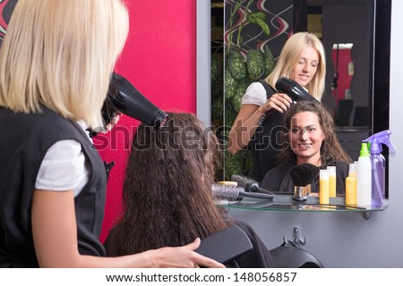 young hairdresser makes hairstyle for beautiful girl in beauty salon - stock photo