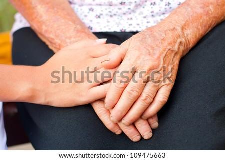 Young hands between elderly ones. - stock photo