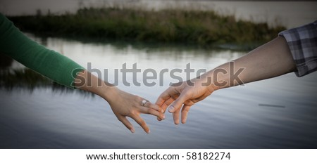 Young hands touching water in background. - stock photo
