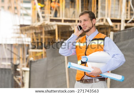 young handsome architect supervising a construction using cell phone - stock photo