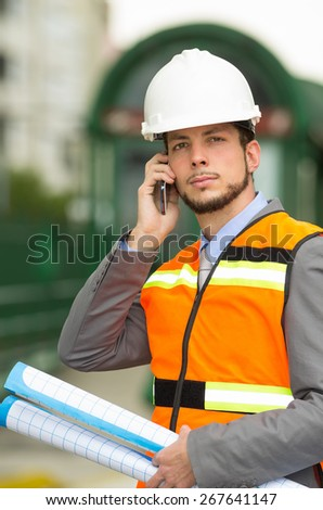 young handsome architect supervising a construction using cell phone outdoors - stock photo