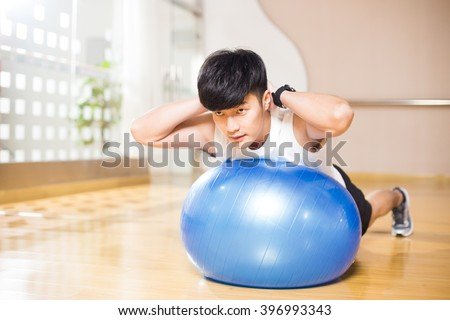young handsome asian man works out in modern gym - stock photo