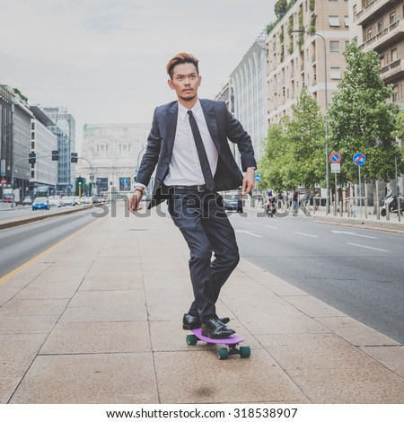 Young handsome Asian model dressed in dark suit and tie riding his skateboard - stock photo