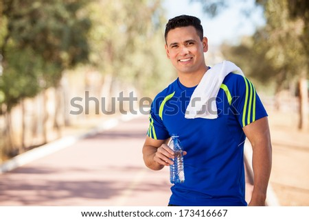 Young handsome athlete resting and drinking water after a run in a running track - stock photo