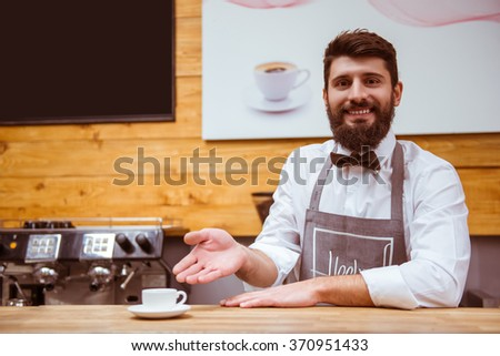 Young handsome barista with beard in shirt and bow tie offering coffee and smiling while standing at the bar counter - stock photo