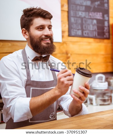 Young handsome barista with beard in shirt and bow tie smiling and writing on a cup while standing at the bar counter - stock photo