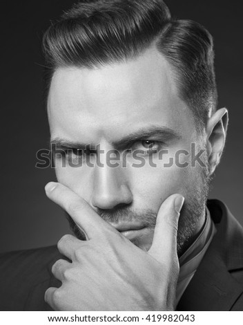 Young handsome bearded caucasian man with blue eyes and a hand near chin. Perfect skin and hairstyle. Wearing blue suit and watch. Studio portrait on gradient black to grey background. Black and white - stock photo