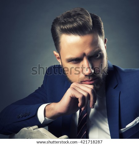 Young handsome bearded caucasian man with blue eyes sitting on chair. Perfect skin and hairstyle. Wearing blue suit and tie. Studio portrait on gradient black to grey background. Toned - stock photo