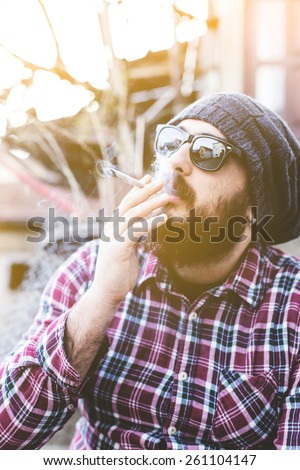 Young handsome bearded hipster man smoking cigarette (pot, marijuana, ganja) in the city - stock photo