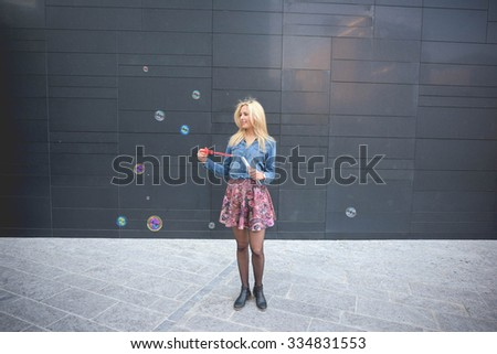 Young handsome blonde caucasian girl having fun playing with soap bubble in the city wearing jeans shirt and floral skirt - emancipation, carefree, youth concept - stock photo