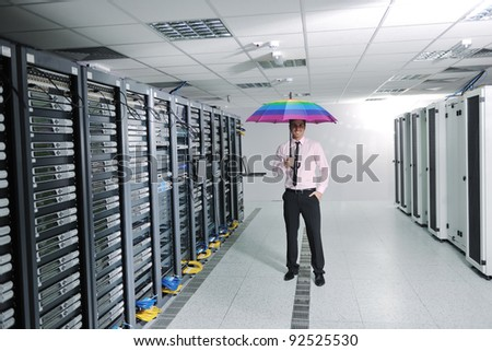 young handsome business man  engineer in .businessman hold  rainbow colored umbrella in server datacenter room  and representing security and antivirus sofware protection concept - stock photo