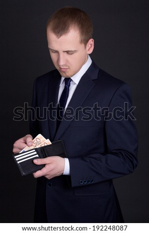 young handsome business man holding leather purse with euro banknotes - stock photo