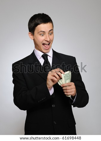 Young handsome business man in black suit and tie counting money. gray background - stock photo