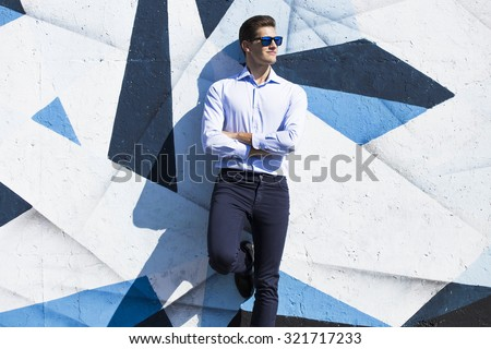 Young handsome business  man in blue  suit and glasses watching against painted wall. - stock photo
