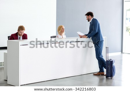 Young handsome businessman flirting with female receptionist - stock photo