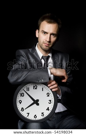young handsome businessman holding big clock - stock photo